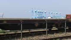 Freight train, empty wagons passing by, seaport container terminal in background - stock footage