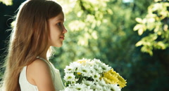 Closeup portrait girl in wite dress standing in the park and holding bouquet - stock footage