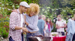 4K Happy man & woman chat at bbq while friends socialize in the background Stock Footage