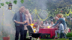 Happy attractive couple cooking at bbq while friends socialize in the background - stock footage