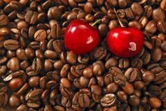 Toasted coffe beans and red cherry Stock Photos