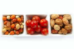 Triple bowl with varied japanese snacks and tomatoes Stock Photos