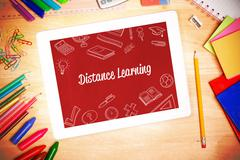 Distance learning against students desk with tablet pc Stock Photos