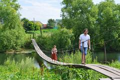 People walk on  suspension bridge over the river Stock Photos