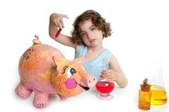 Little girl pretending be veterinary with a pig - stock photo