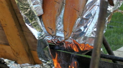 A fire in the bottom helps the hotdog be cooked - stock footage