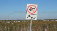 No littering sign with giant chimney in the background. Sudbury, Ontario. Stock Footage