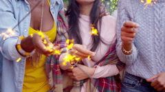 Joyful mixed ethnicity female friends holding sparklers at outdoor party Stock Footage
