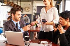 Two business people with laptop paying in a coffee shop Stock Photos