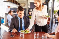 Business man being served food in a restaurant Stock Photos