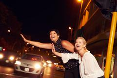 Female friends hailing taxi on city street at night Stock Photos