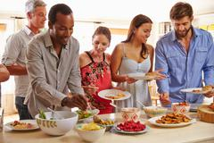Friends serving themselves food and talking at dinner party - stock photo