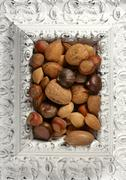 Wooden decorated classic white frame, varied nuts Stock Photos