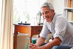 Portrait of a smiling grey haired man sitting in a room - stock photo