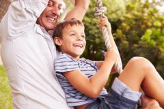 Father swinging with son at a playground Stock Photos