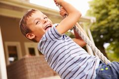 Smiling boy swinging on a rope at a playground Stock Photos