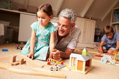 Father playing with kids and toys in an attic playroom - stock photo