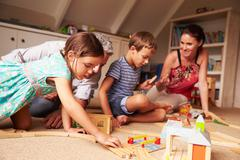 Parents playing with kids and toys in an attic playroom - stock photo