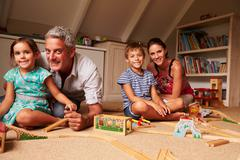 Family playing with toys in an attic playroom, portrait - stock photo