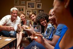 Group of friends sitting around a table at house party - stock photo