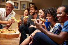 Friends eating pizza at a house party, watching television - stock photo