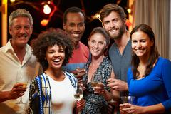 Adult friends drinking at a house party, group portrait - stock photo