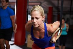 Woman In Gym Exercising With Gymnastic Rings Stock Photos