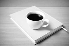 Coffee cup on orange book black and white color tone style Stock Photos