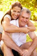 Senior man embraced by his adult daughter, outdoors - stock photo