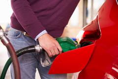 Refuelling a car at a petrol station, close up - stock photo