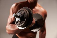 Male bodybuilder working out with heavy dumbbell, crop Stock Photos