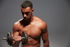 Muscular young man working out with a heavy dumbbell Stock Photos