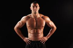 Smiling bare chested male body builder with hands on hips Stock Photos