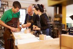 Senior shoemaker training apprentices to make shoe lasts - stock photo