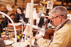 Shoemaker stitching leather in a workshop - stock photo