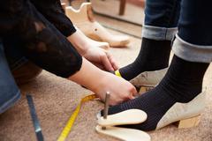 Shoemaker measuring customers feet, close up Stock Photos