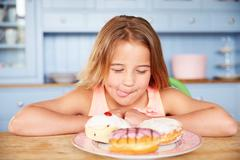 Young Girl Sitting At Table Looking At Plate Of Sugary Cakes - stock photo