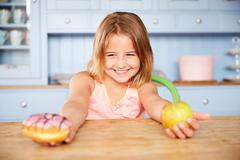 Girl Sitting At Table Choosing Cakes Or Apple For Snack Stock Photos