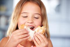 Young Girl Sitting At Table Eating Sugary Donut - stock photo