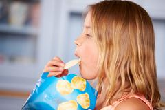 Young Girl Sitting At Table Eating Potato Chips Stock Photos