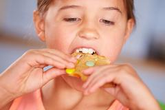 Close Up Of Young Girl Sitting At Table Eating Cookie Stock Photos