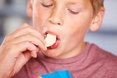 Close Up Of Boy Eating Packet Of Potato Chips Stock Photos
