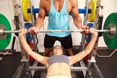 Woman bench pressing weights with assistance of trainer, front view Stock Photos