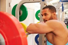 Man leaning on barbells in a rack after weightlifting at gym - stock photo