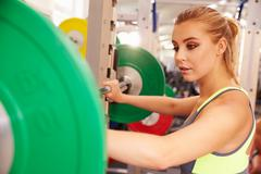 Woman preparing to lift barbells at a squat rack in a gym Kuvituskuvat
