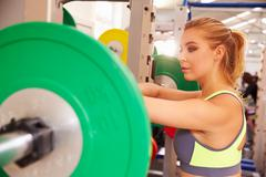 Woman leaning on a barbells at a squat rack in a gym Kuvituskuvat