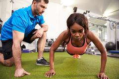 Young woman doing push ups under supervision of a trainer Stock Photos