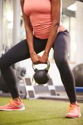 Woman exercising in a gym with a kettlebell weight, crop Stock Photos