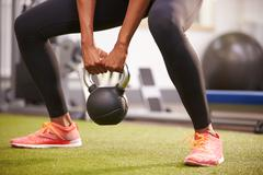 Woman exercising with a kettlebell weight, low-section crop Stock Photos