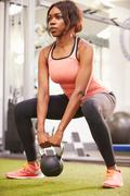 Woman exercising in a gym with a kettlebell weight, vertical Stock Photos